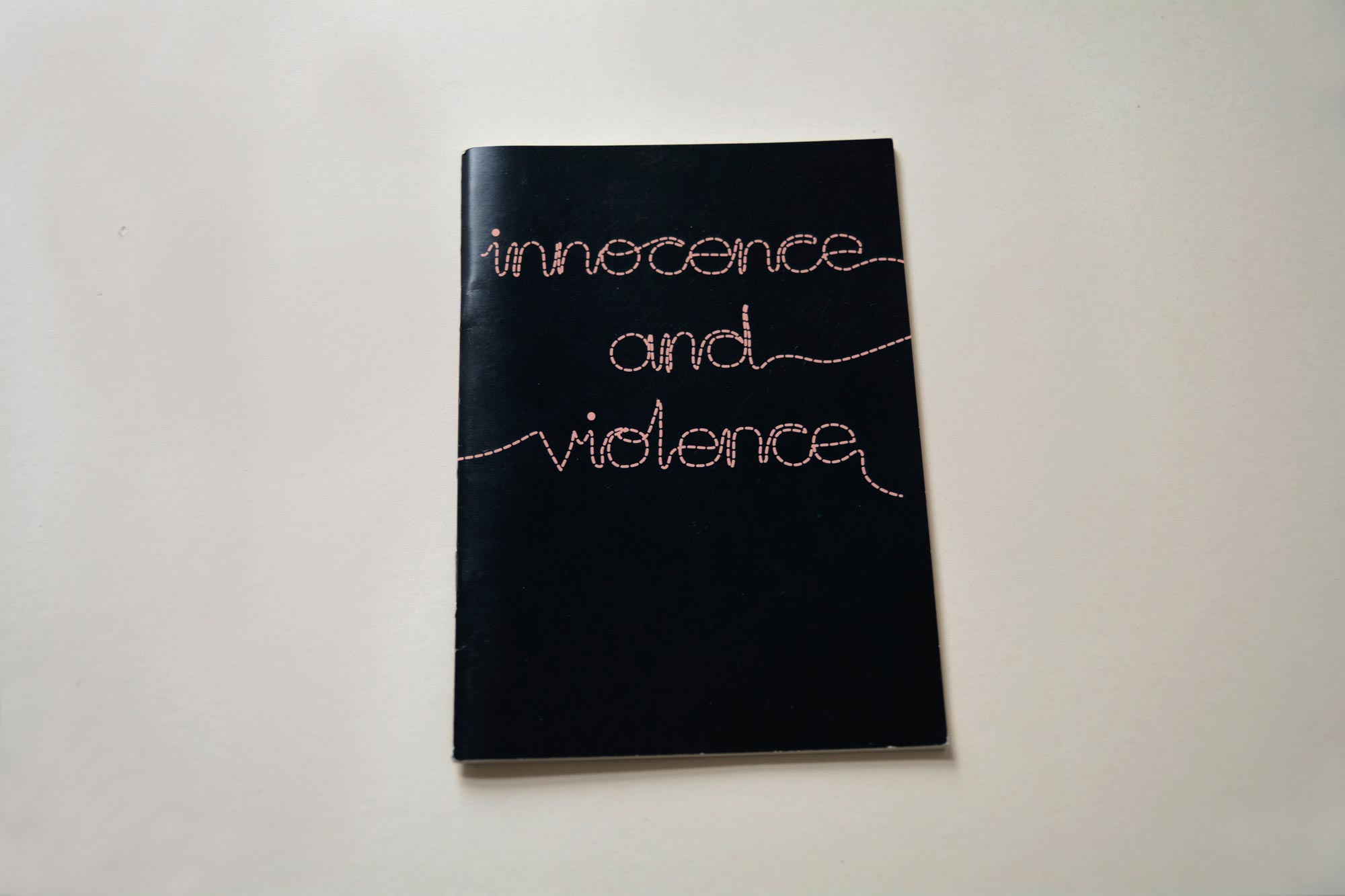 Cover cataloge. Full black background. Large Title written in a stitched-look script font.