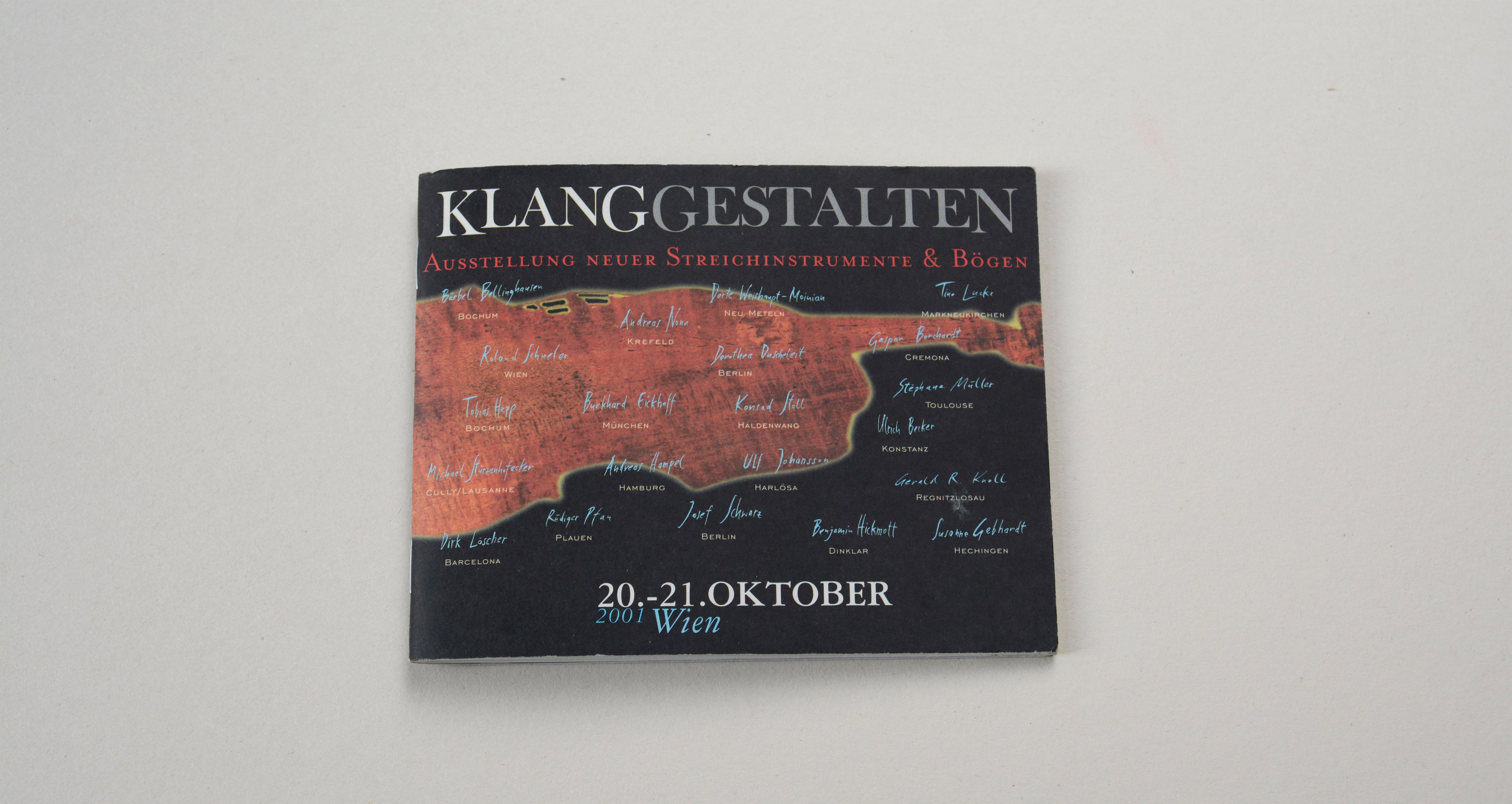 Cover catalogue landscape format. Black background. Large silhouette of violin in the middle. Large logo/title above. Line of text underneath. Several signatures overlayed on entire cover.