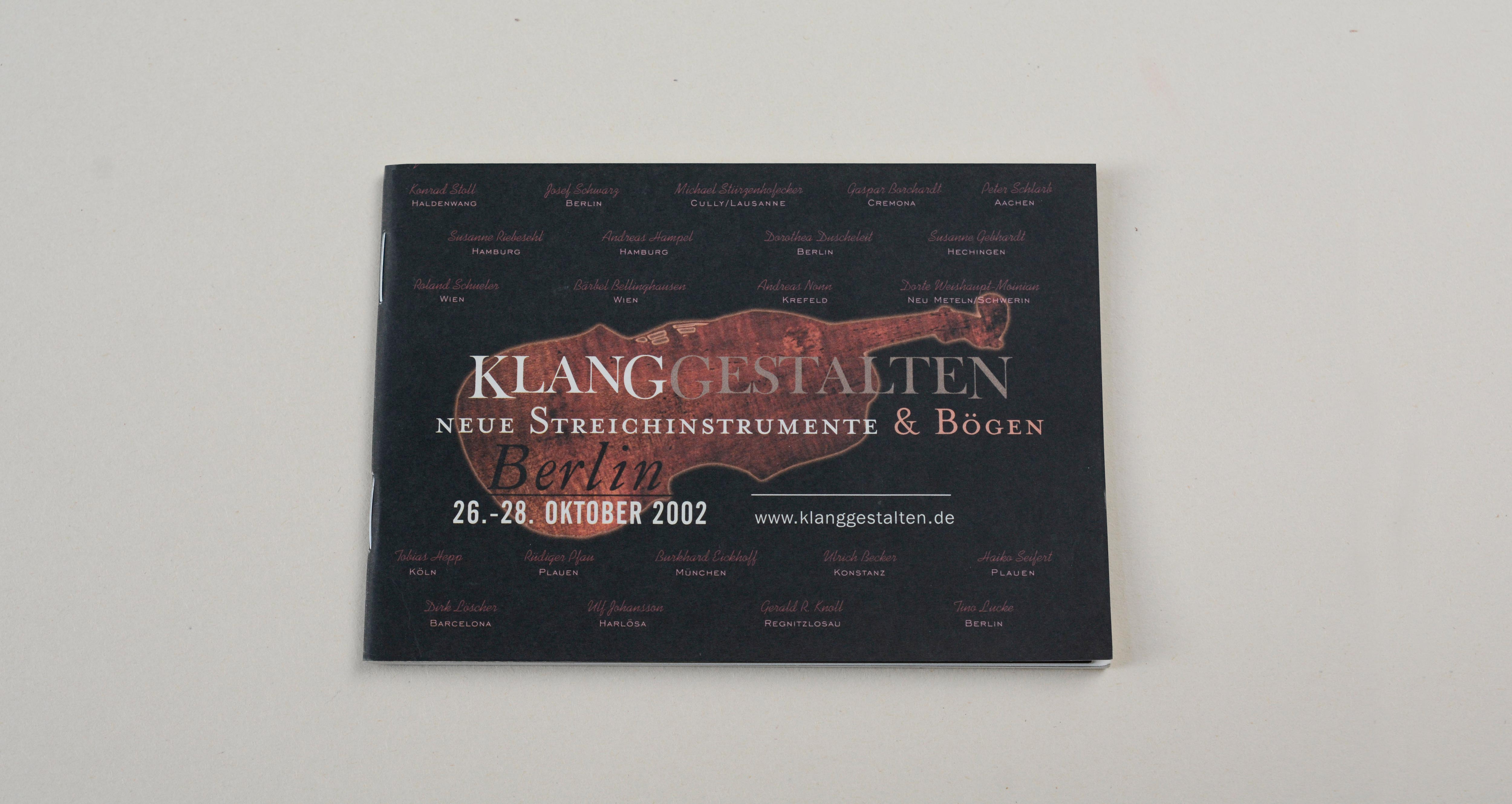 Cover catalogue landscape format. Black background. Large silhouette of violin in the middle. Large logo/title and line of text overlayed. Several signatures overlayed on entire cover.