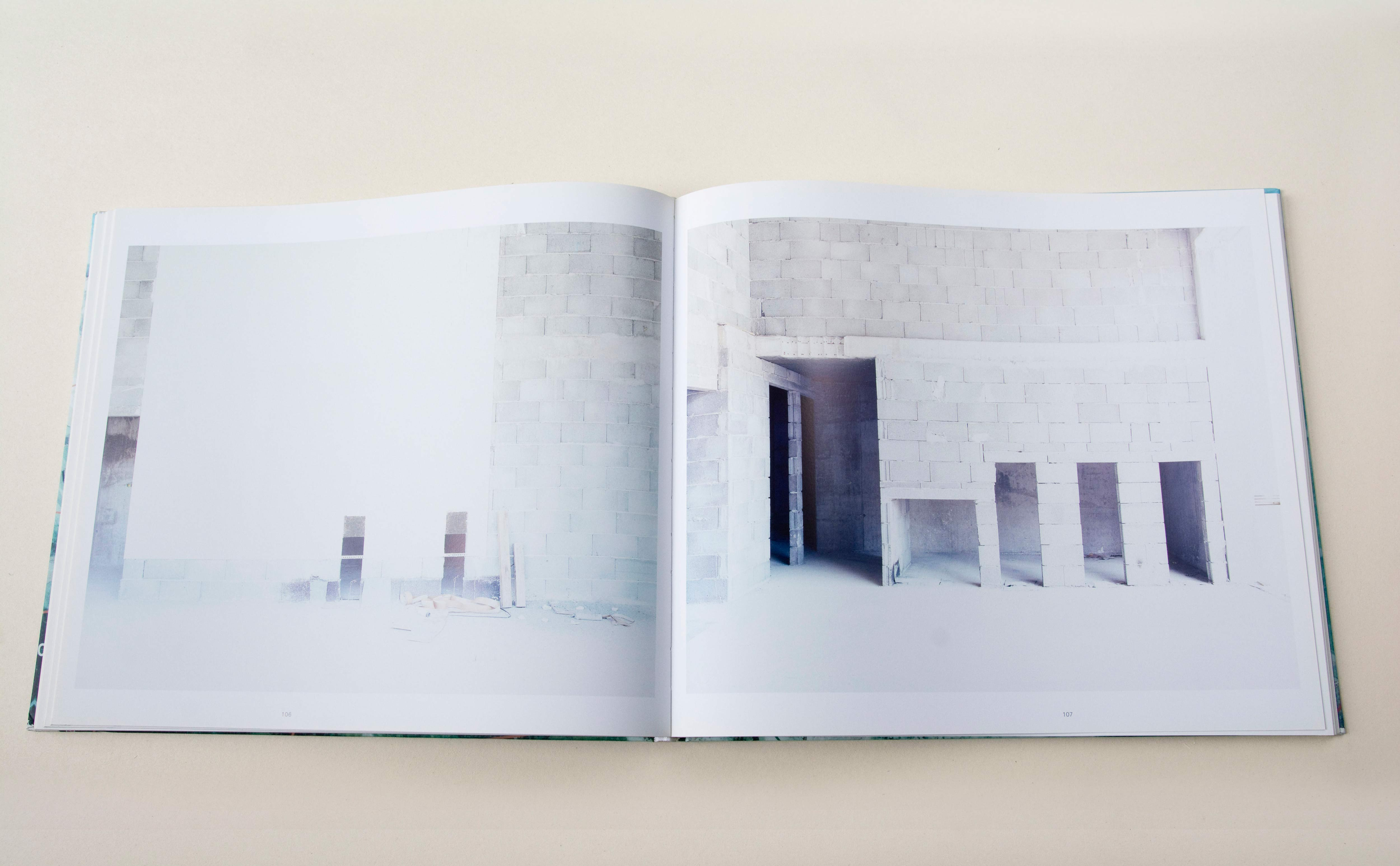 Double page. Large photo with white space around on each page. Left: Grey brick wall in construction. Right: Inside a building made of grey bricks.