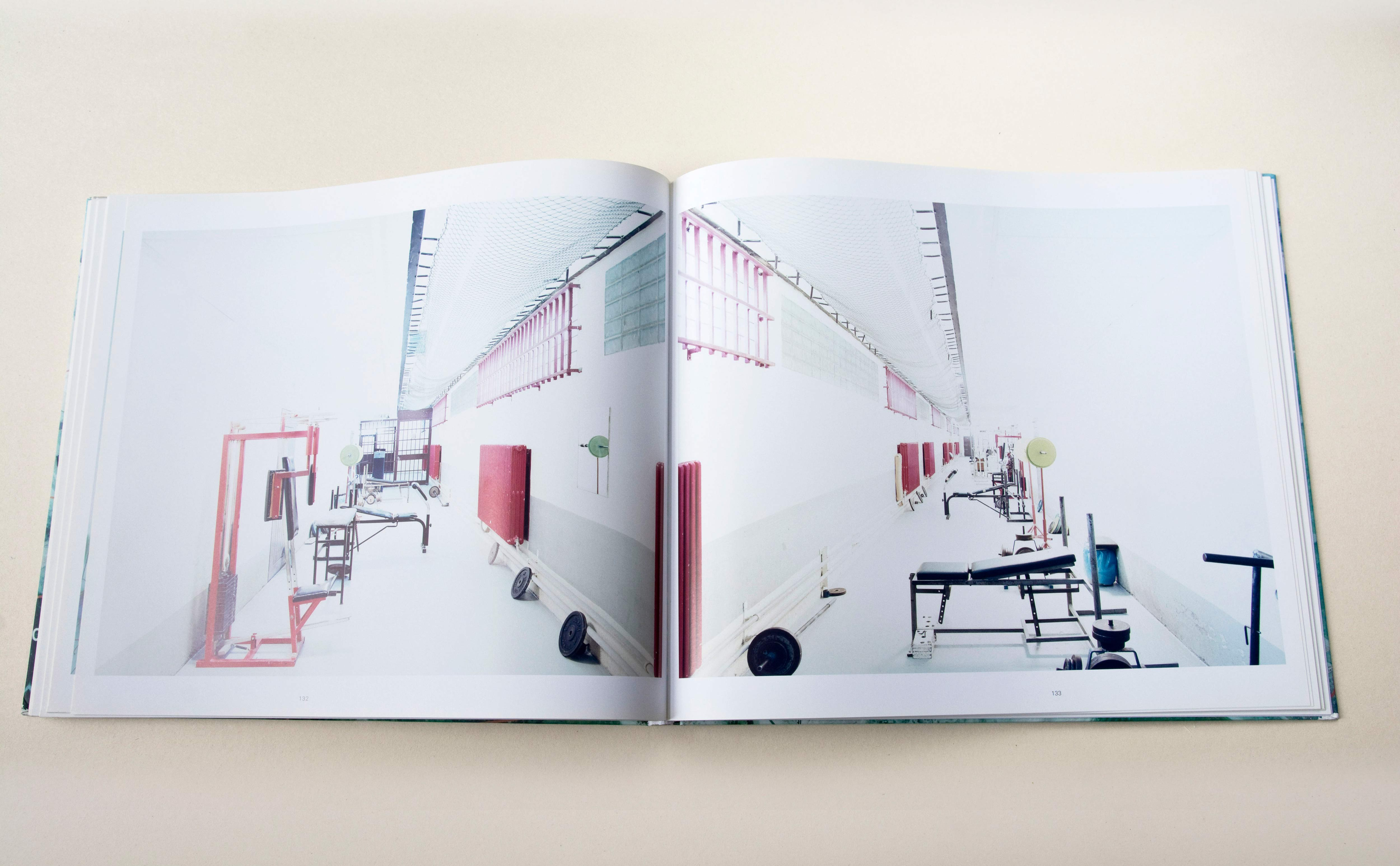 Double page. Large photo with white space around on each page. Left: Corridor in a prison. Fitness devices standing at the side. Right: Similar shot of corridor mirrorerd.