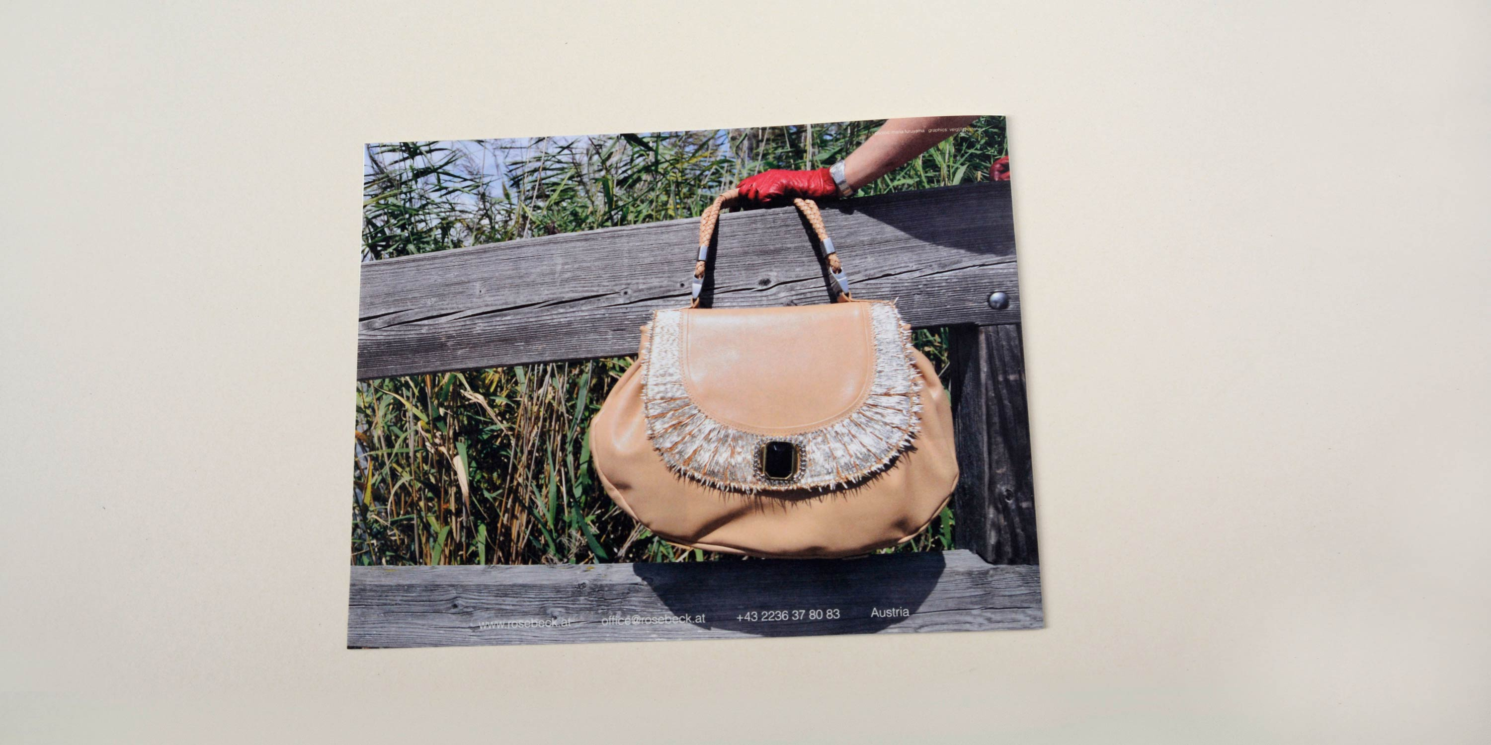 Back catalogue. Full-page photo hand holding large handbag in front of wooden railing. Reeds in the background. Row of small text at bottom overlayed.